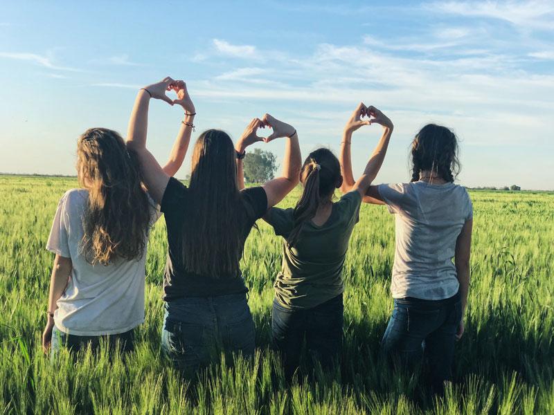 Four ladies in a field celebrating Ohana Membership