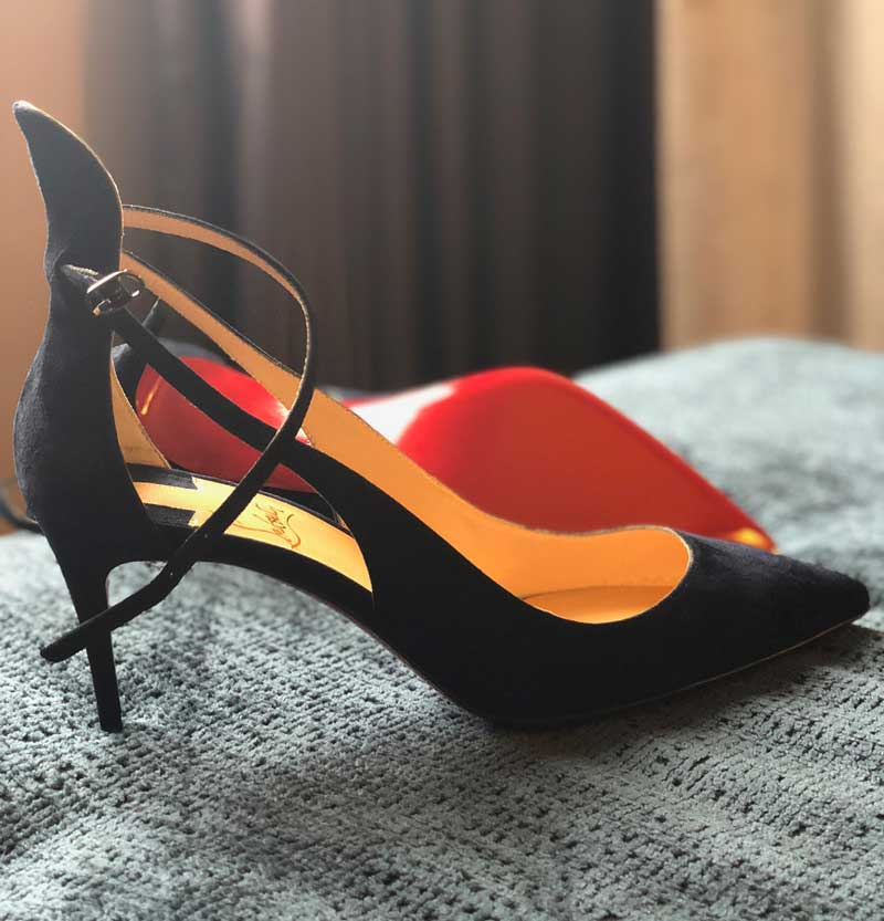 Louboutin red bottomed shoes on bed
