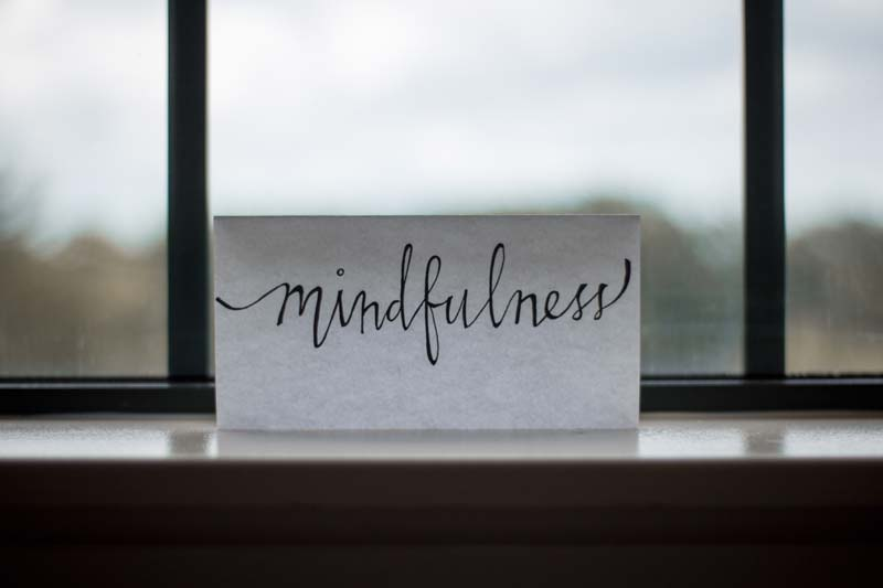 mindfulness written on a piece of paper in front of a window