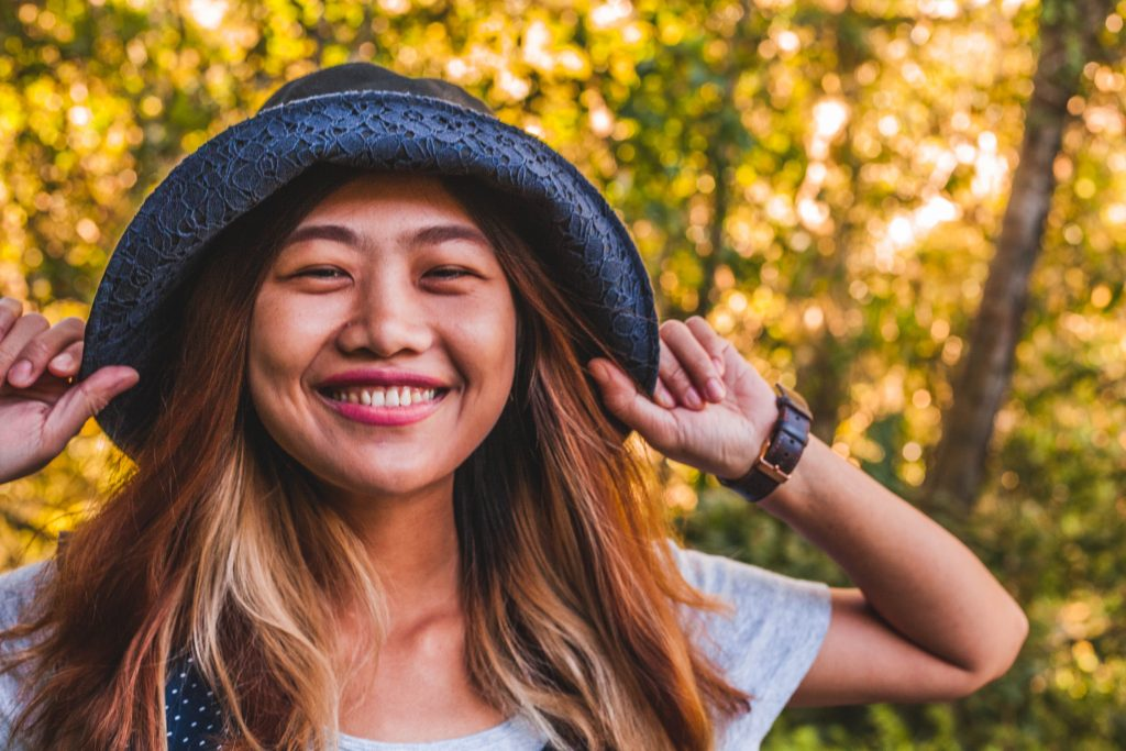 Smiling Asian women in hat and short sleeves smiling outdoors